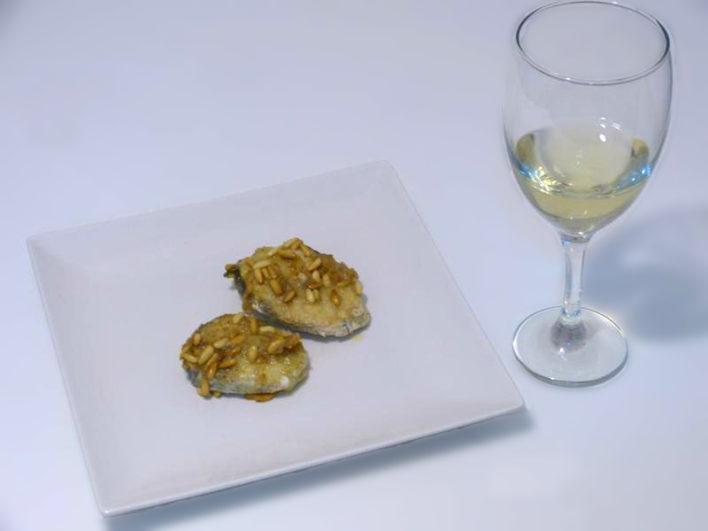 Presentación de la merluza en salsa de piñones