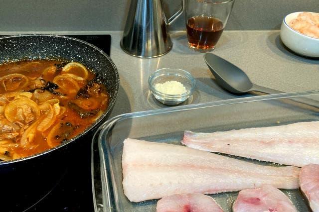 Preparamos la bandeja con la merluza, la salsa de cebolla, el queso y el perejil - Destino Castilla y León